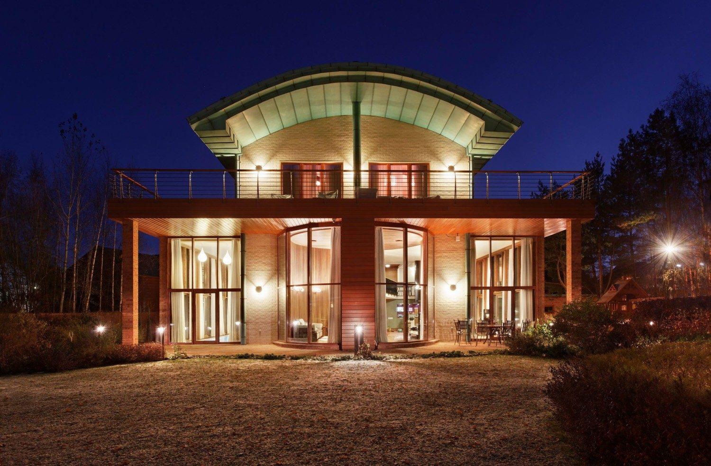 Вид на загородный дом ночью с подсветкой